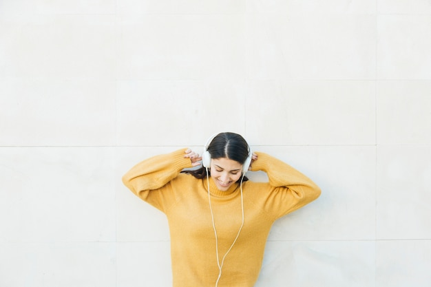 Woman standing in front of wall listening music on headphones