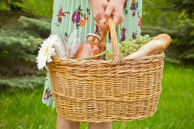 Woman standing on the green grass and holding picnic basket with food, drinks and flower