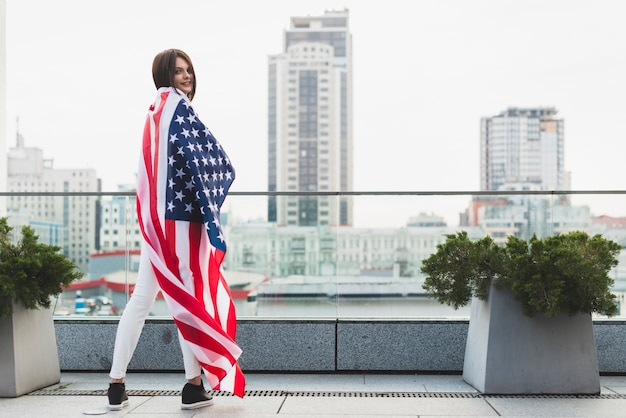 Woman standing in half-turn with big usa flag