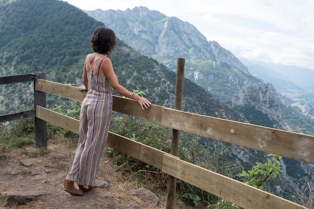 Woman standing on her back leaning on wooden railing in beautiful asturian landscape