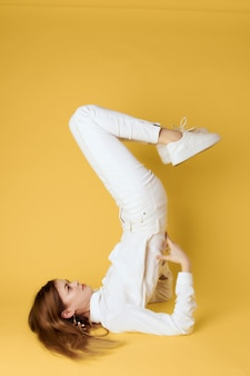 Woman standing on her back with her legs raised upside down gold background