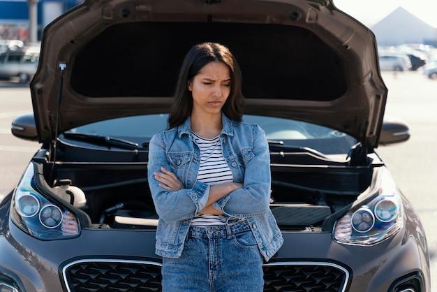 Woman standing next to her broken car