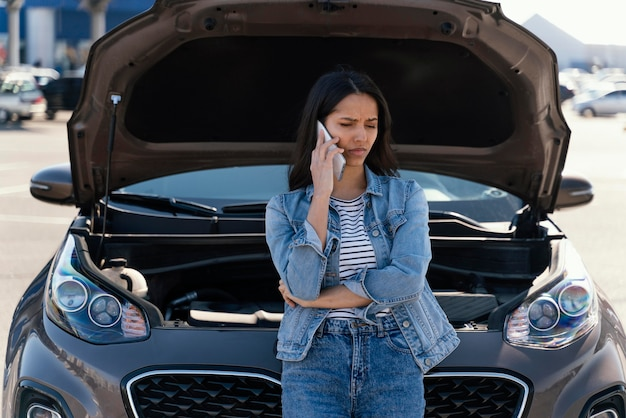 Donna in piedi accanto alla sua macchina rotta