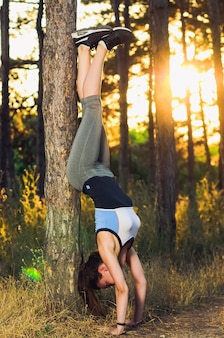 Woman standing on her hands while her legs leaning on tree