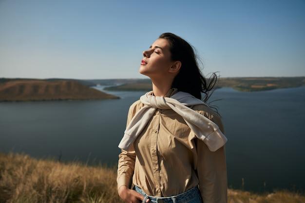 ドニエストル川の素晴らしい景色を眺めながら高く立っている女性