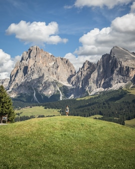 Woman standing on a hill with the plattkofel mountain as backgound in compatsch italy