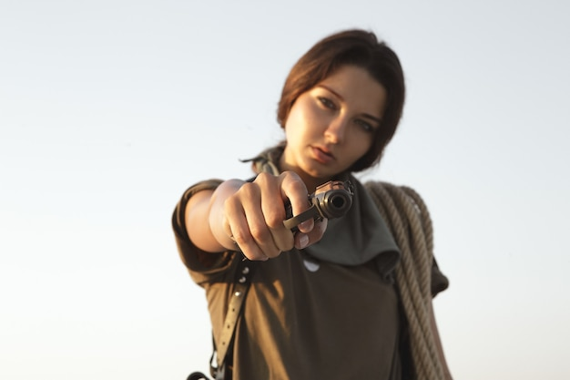 砂漠の屋外で銃とロープを持って立っている女性。若い残忍な肖像画