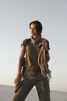Женщина, стоящая с пистолетом и веревкой на открытом воздухе в пустыне. молодая жестокая опасная девушка с ружьем