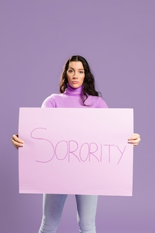 Woman standing and holding sorority cardboard