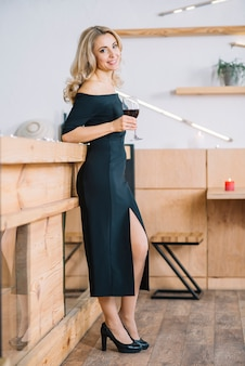 Woman standing and holding wine glass