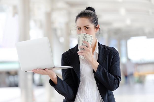 Женщина стоя держащ работу с компьтер-книжкой и деньгами