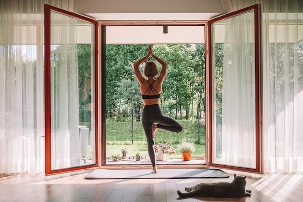 Женщина, стоящая в позе дерева перед открытым окном, занимается йогой дома. ее кот смотрит на нее, лежа рядом с ней.