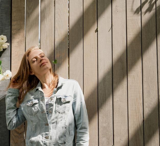 木製の壁と自然光の中に立っている女性