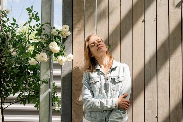 白いバラと自然光と木製の壁に立っている女性
