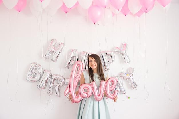 생일 파티를 위해 풍선과 색종이 조각으로 장식된 곳에 서 있는 여자