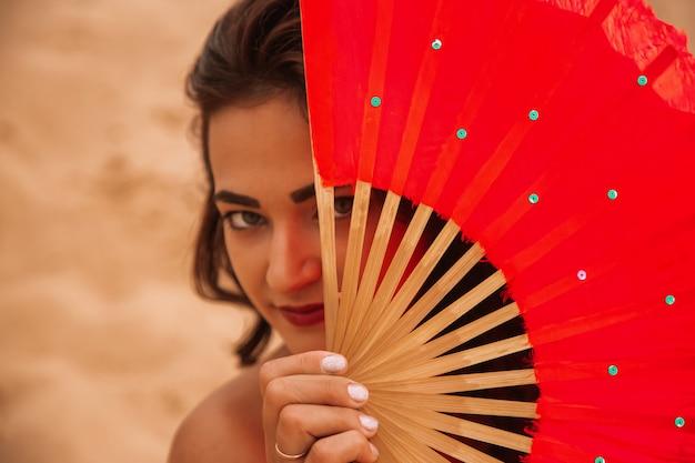 Женщина, стоящая в пустыне с красными вентиляторами. портрет крупным планом