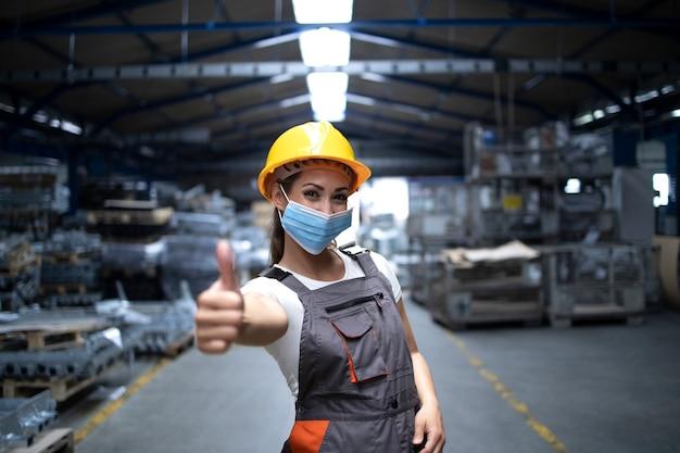 Женщина стоит в заводском цехе и показывает палец вверх в гигиенической маске как профилактика от вируса короны