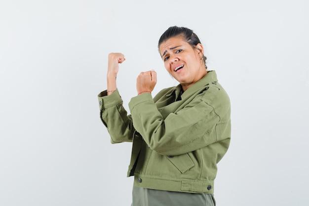 Женщина, стоящая в бою, позирует в куртке, футболке и выглядит уверенно. .