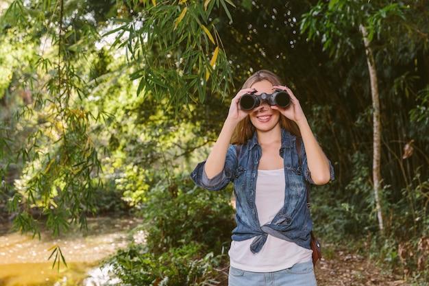 쌍안경을 통해 찾고 숲에 서있는 여자