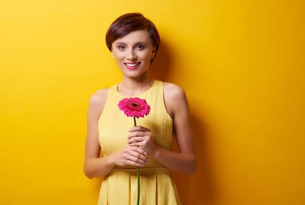 꽃과 함께 카메라 앞에 서 있는 여자