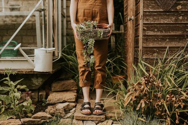 관엽 식물과 함께 창고 앞에 서있는 여자