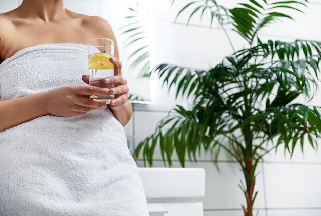 洗面台の前に立って、バスルームにレモンと注入された水のガラスを保持している女性。トリミングされた肖像画。