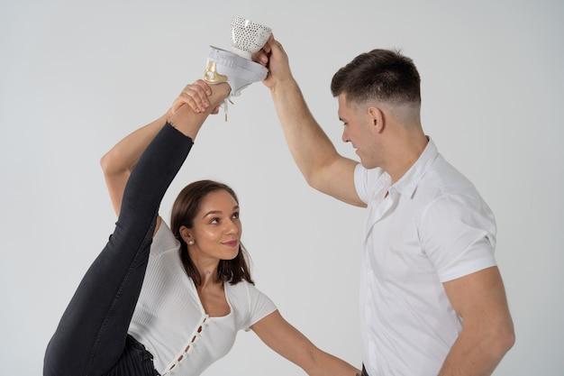 Женщина, стоящая в гимнастике, раскололась, и мужчина рядом с чашкой с напитком, изолированной на белом ...