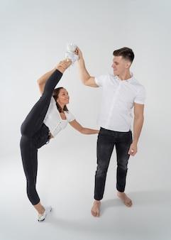 Женщина, стоящая в разделенной гимнастике, и мужчина, держащий чашку с напитком на ее пригонке, изолированном на белом. концепция здорового образа жизни и творчества.
