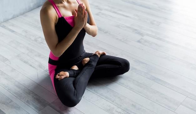 Женщина стоя в представлении йоги лотоса с руками против ее комода