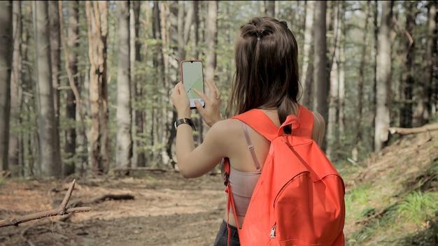 숲 한가운데 서서 스마트 폰의 내비게이션 앱을 사용하여지도의 도움으로 경로를 따라가는 여성
