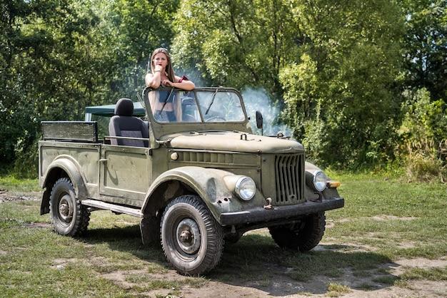 屋外でポーズをとる軍用車に立っている女性