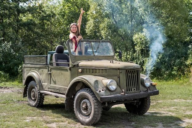 야외 포즈 군사 차에 서있는 여자