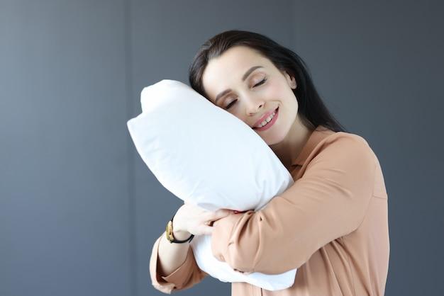 枕に頭を抱えてオフィスに立っている女性