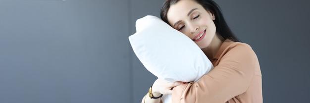 Женщина, стоящая в офисе с головой на подушке