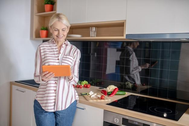 キッチンに立って料理のビデオワークショップをしている女性
