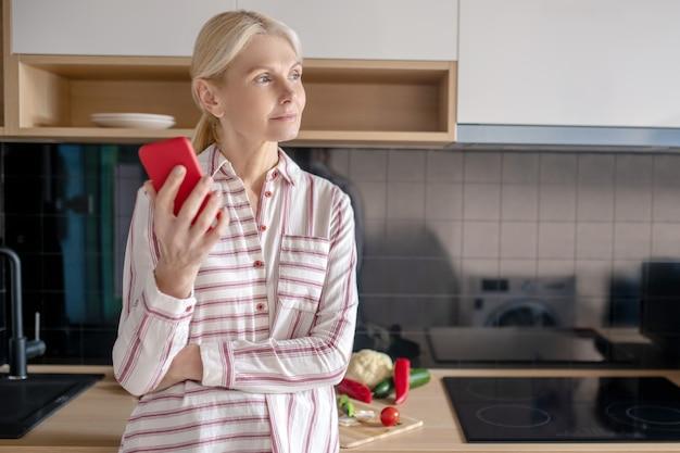 Женщина стоит на кухне со смартфоном в руке и выглядит задумчивой