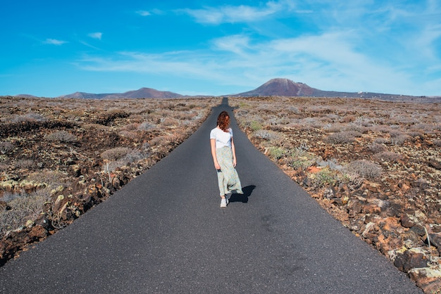 晴れた日に人けのない道の真ん中に立っている女性。