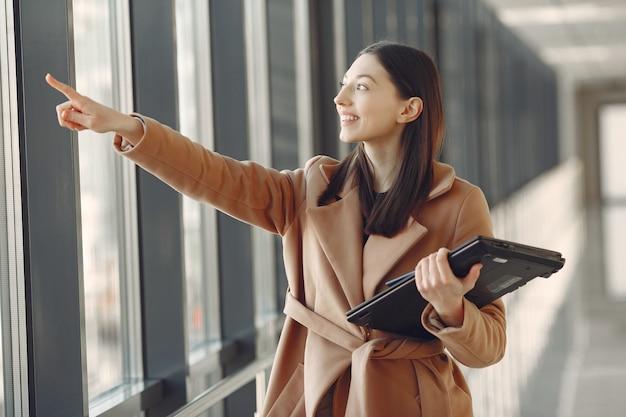 Женщина, стоящая в офисе с ноутбуком