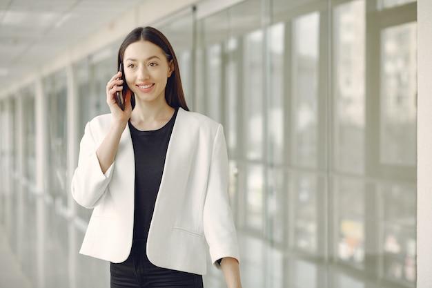 Женщина стоит в офисе с телефоном