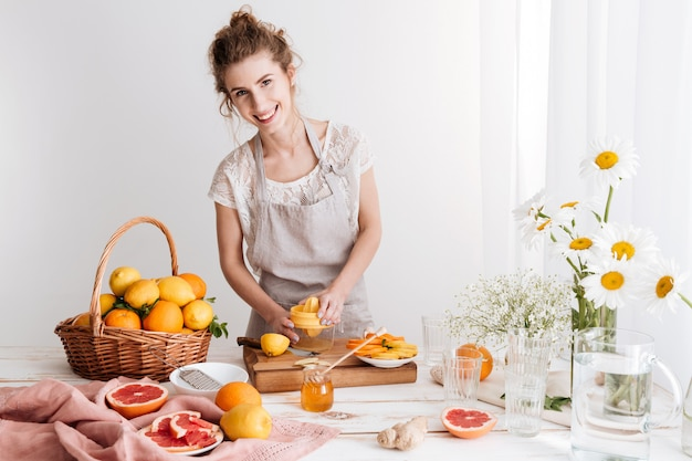 Woman standing indoors and squeezes out juice of a citruses