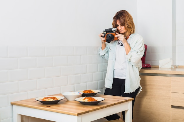 Woman standing in kitchen with camera