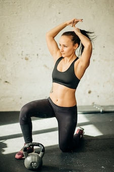 Woman standing on knee and preparing for cross fit exercise