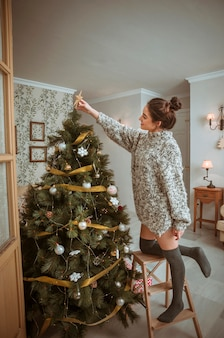 Woman standing on ladder and decorating christmas tree