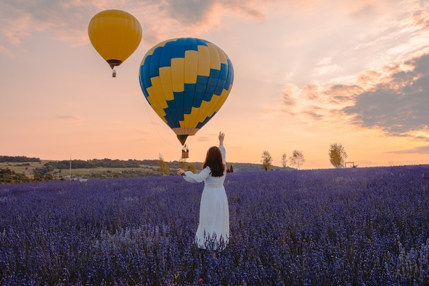 Woman standing at lavender field looking at air balloons with basket sunset time