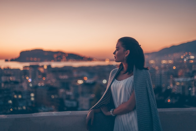 夕日を見て、思慮深く見て立っている女性
