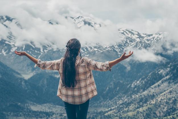 Donna in piedi e guardando le montagne in natura