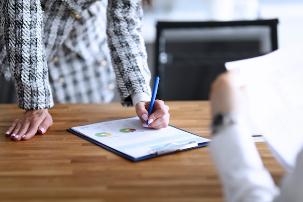 Woman standing looks at report lying on table men