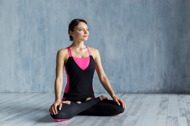 Woman standing in lotus yogapose while looking aside