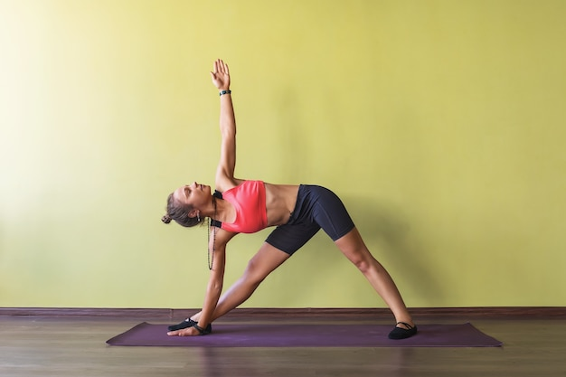 Woman standing on a mat performs the exercise utthita trikonasana near the wall the triangle pose