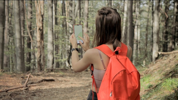Woman standing in middle of forest, using navigation app on smartphone, following route with help of map